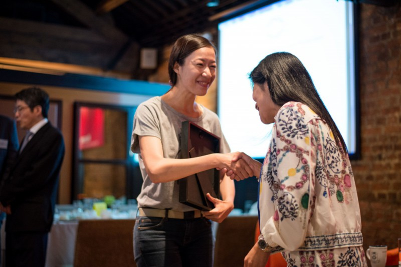 Nora Tam, South China Morning Post photojournalist, gets her prize in photography judge Angela Lee.